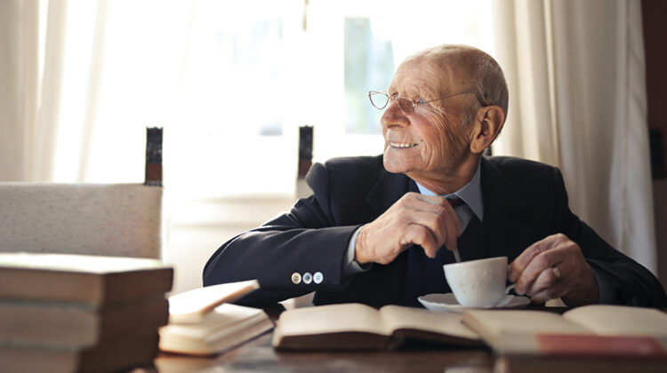 elderly gentleman drinking a hot beverage while sitting at a table with books
