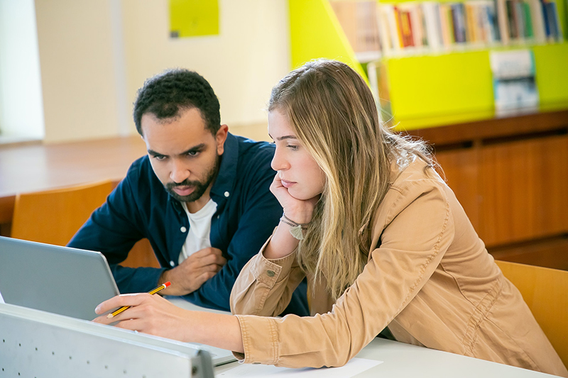 two students in the library studying and preparing for exam