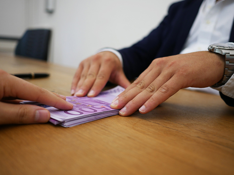 Person receiving cash loan on top of the brown table