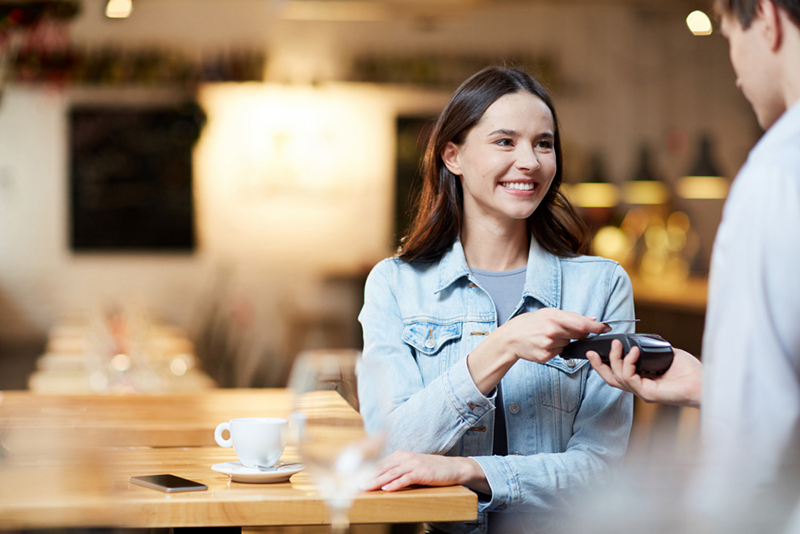 Happy young woman paying order