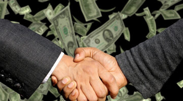 Two businessman handshaking with dollar notes on background