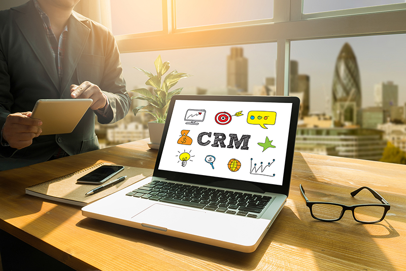Man sitting near laptop with CRM concept on the screen
