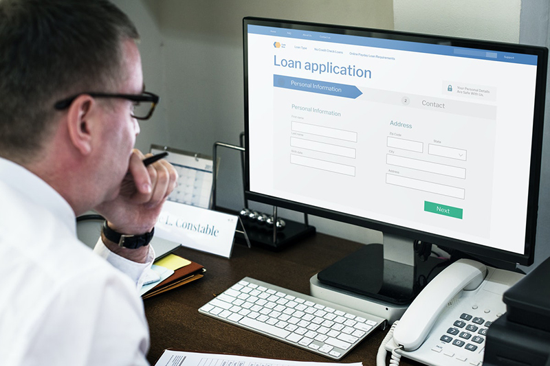 Businessman applying for an online loan on a computer