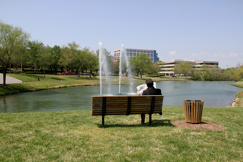 Person reading newspaper on bench in park near pond and fountain
