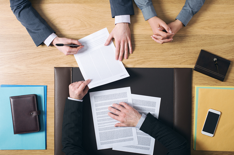 Business man and woman sitting at independent agents office desk and signing important documents, hands top view