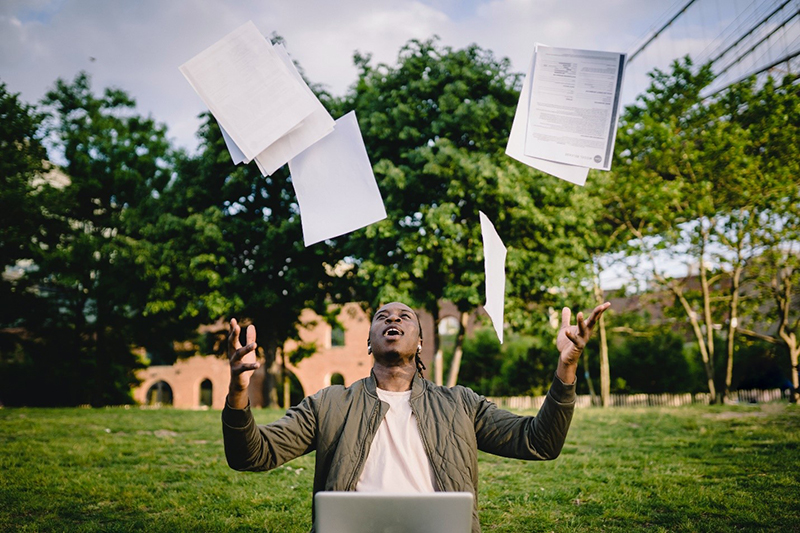 Man sitting in front of his laptop while throwing out documents
