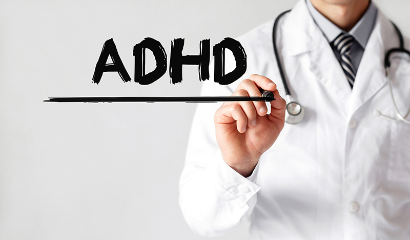 Doctor writing word ADHD with marker