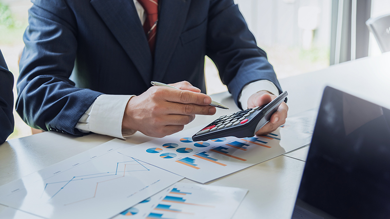 Businessman holding pen and calculator