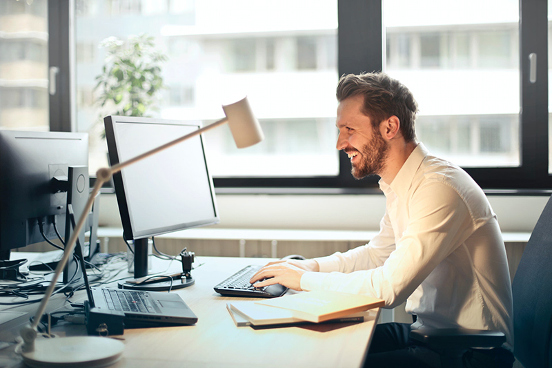 Smiling man working in front of his desk