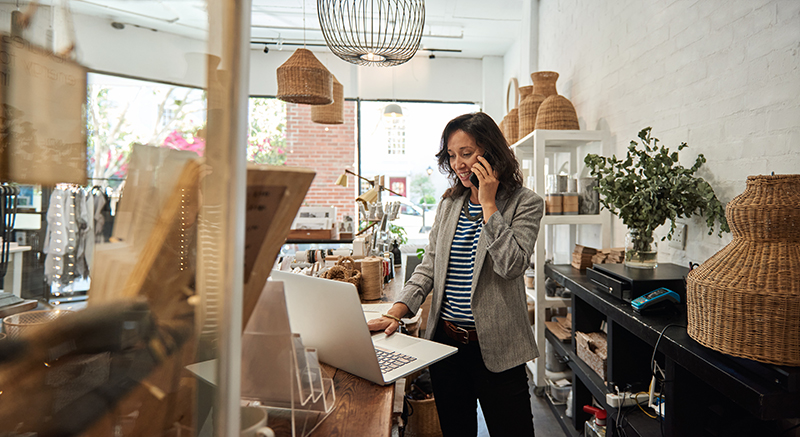 Smiling Asian woman talking on a cellphone in her store