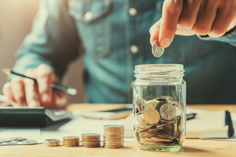 businessman holding coins putting in glass. concept saving money for finance accounting