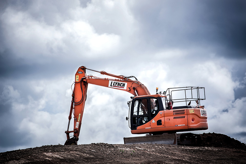 Orange excavator in the middle of wide land area