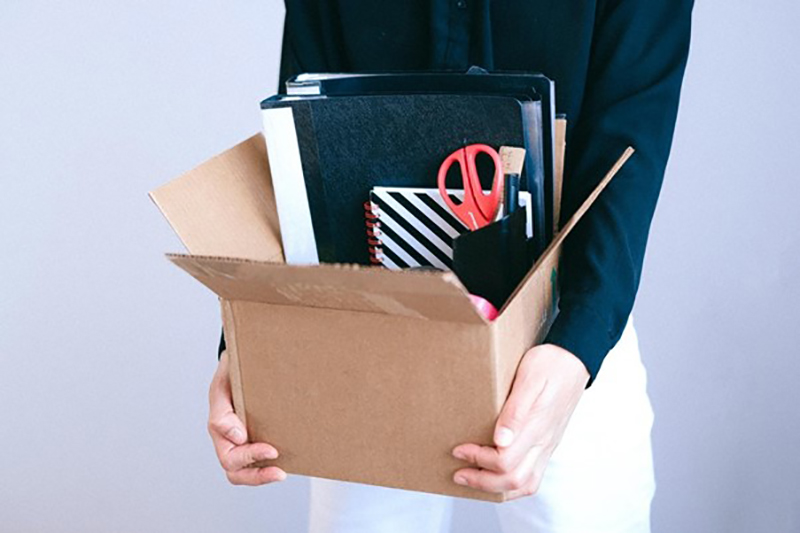 Person carrying box with office stuff