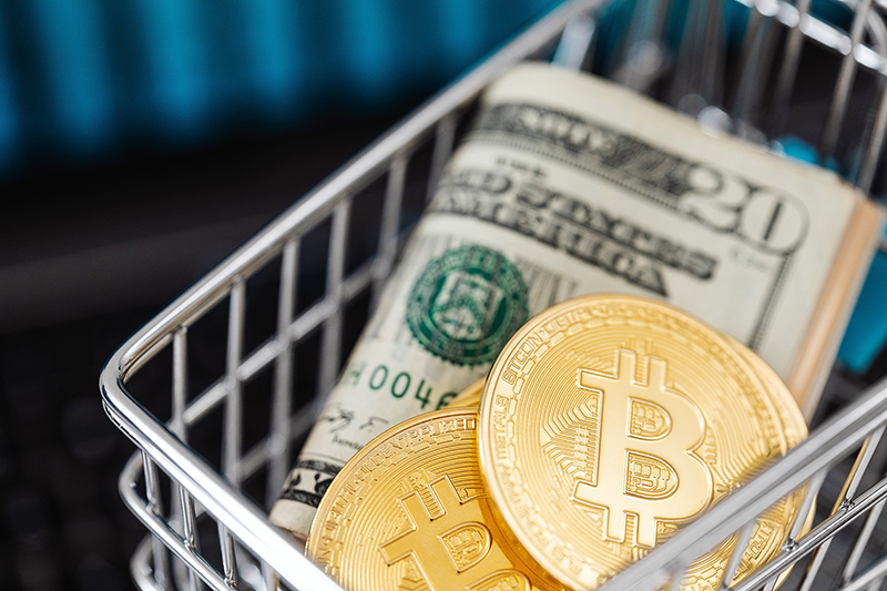 Bitcoin cryptocurrency in mini shopping trolley with dollar bills