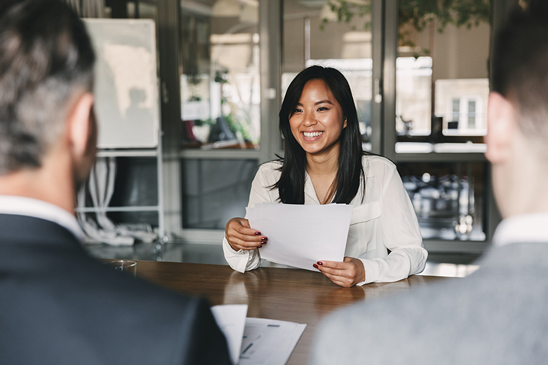 young asian woman smiling and holding resume, while sitting in front of directors during corporate meeting or job interview