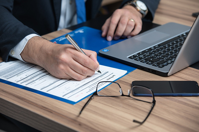 Lawyer signing a document in front of his laptop