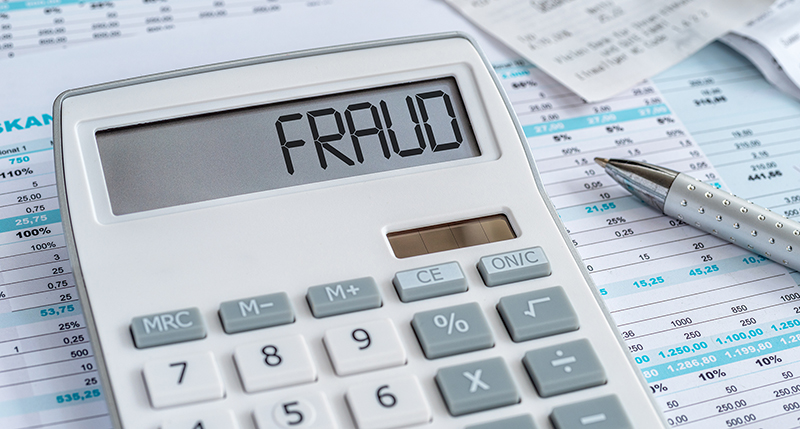 A calculator with the word Fraud on the display