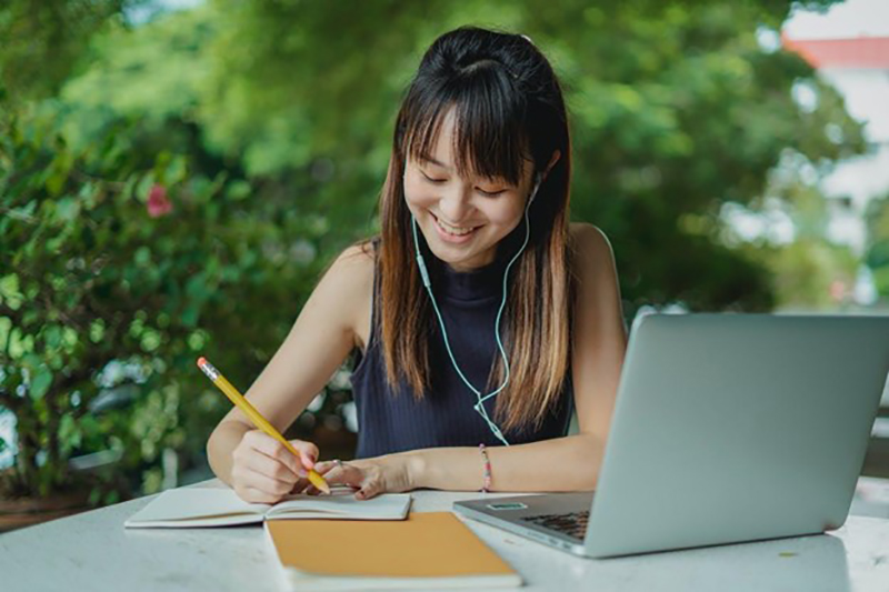 Young asian girl writing on her notepad while wearing headset