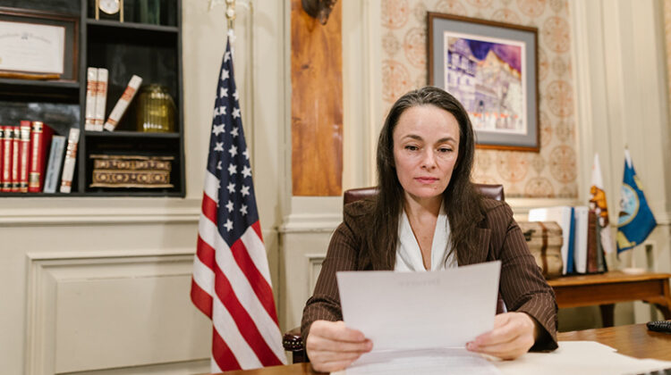 Woman lawyer reading documents sitting inside lawyer office