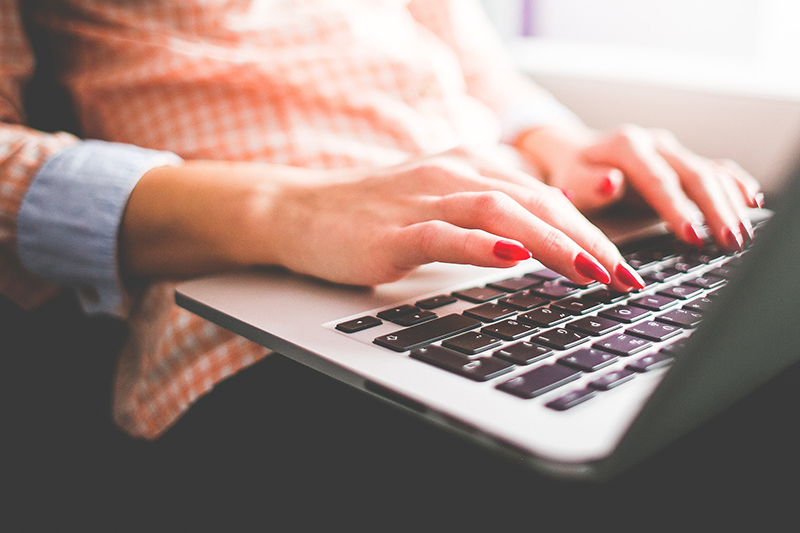 Woman with red nail polished typing on her laptop