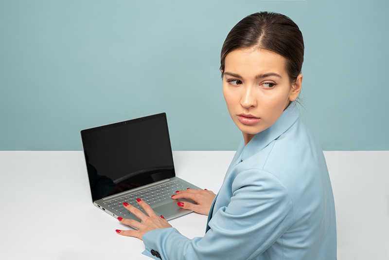 woman using laptop and looking over her shoulder – cybersecurity concept