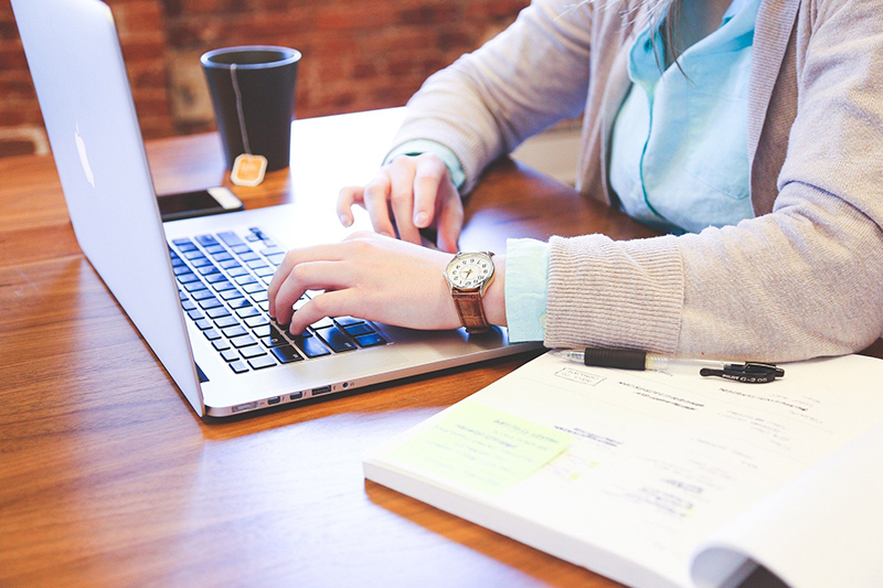 Woman using laptop on top of brown wooden table