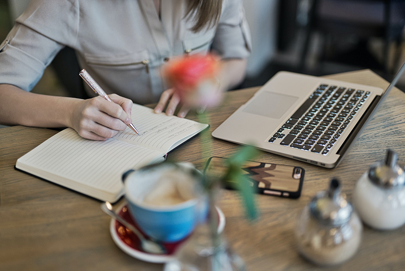person writing content in notebook beside macbook