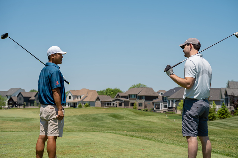 Two men in shorts and t-shirts on the golf course- playing golf