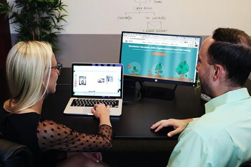Woman and man working in front of two laptops