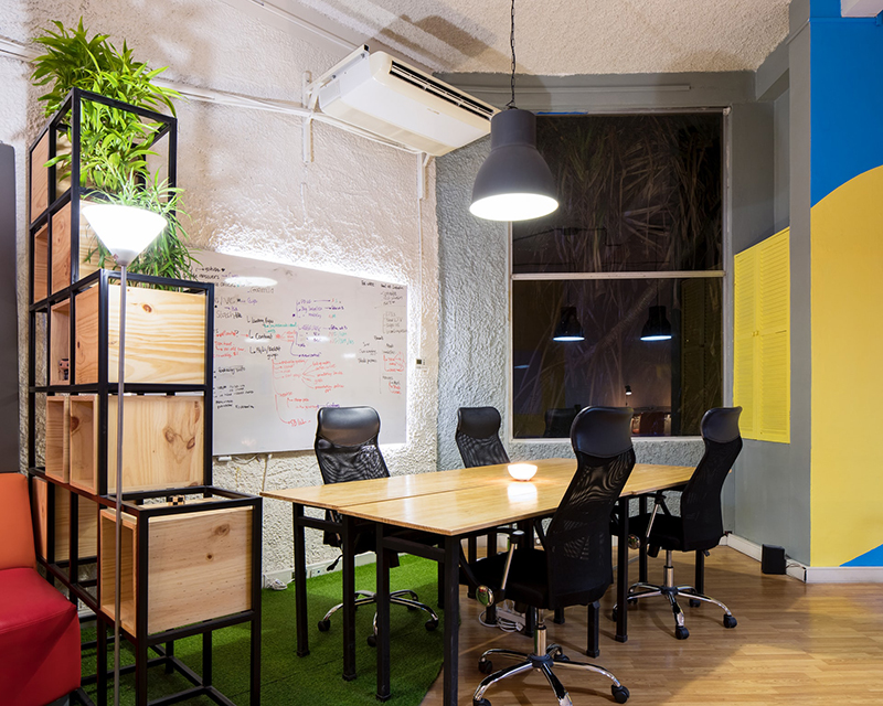 Startup office with desk, and black chairs. Whiteboard beneath HVAC system on the wall.
