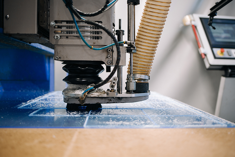 Milling cutter cuts plastic part on robotized production line.