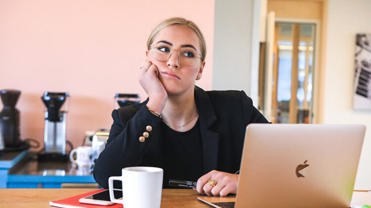 Woman bored and tired in fron t of her laptop
