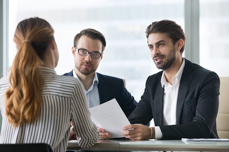 Two male hr managers at interview with female applicant. Man with resume in hands asks questions to candidate. Hiring, staff recruiting process.