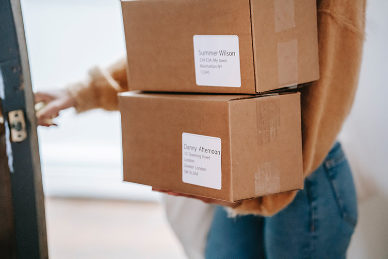 Woman carrying two boxes for delivery