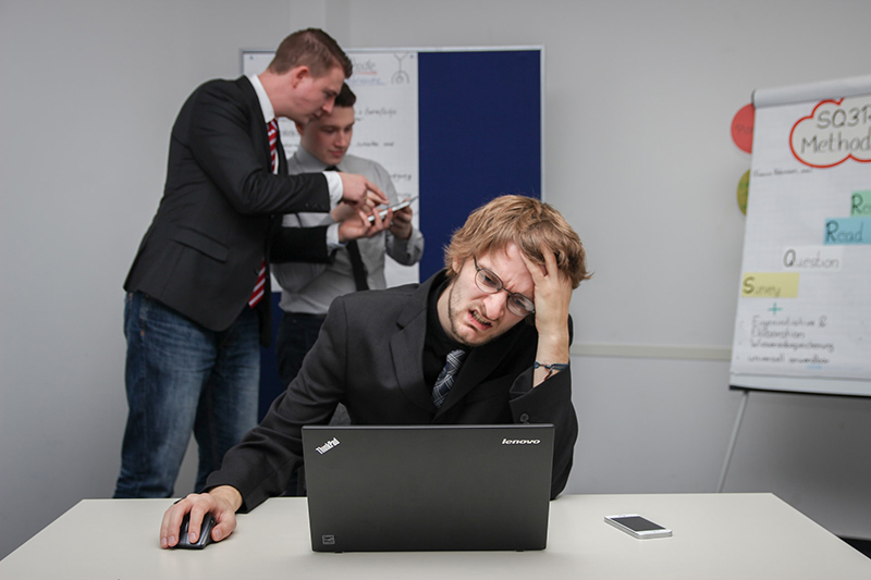 Man sitting on chair in front of his laptop while hands on his head