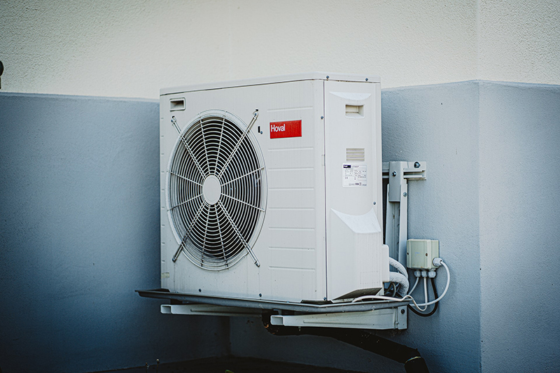 White and grey air conditioning unit attached to a wall