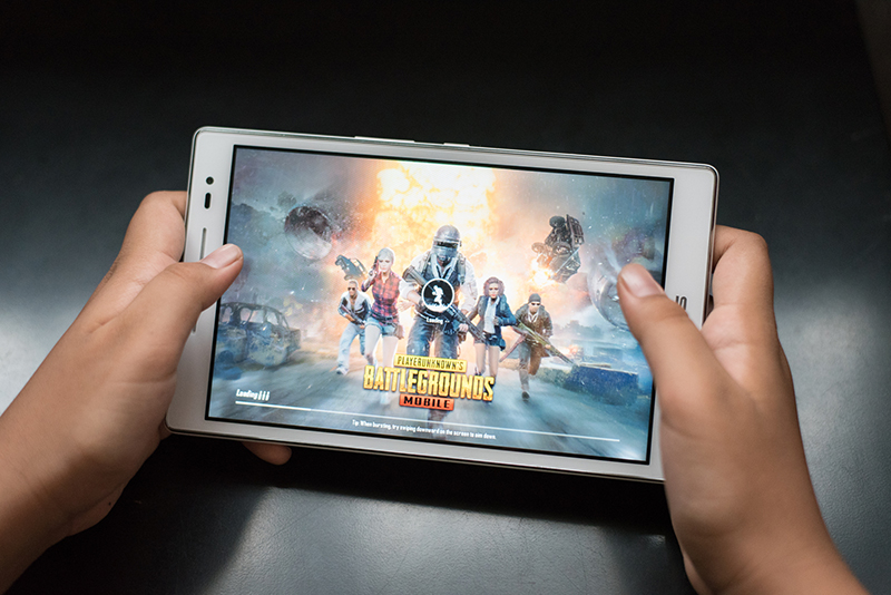 Boy holding a digital tablet playing online mobile game called PUBG