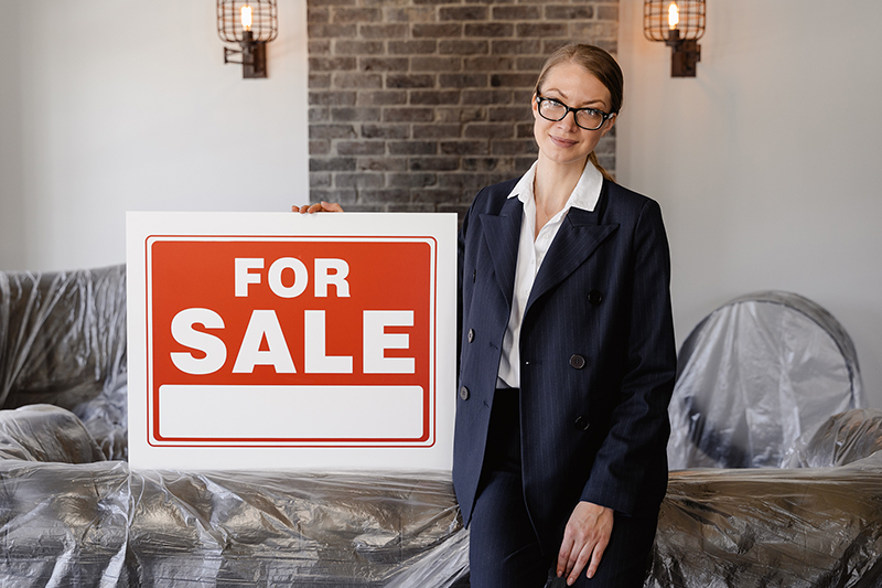 Woman wearing black suit and eye glasses holding for sale banner