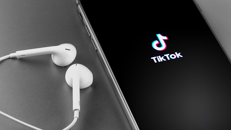 TikTok logo on the screen iPhone with Earpods. TikTok is app to create and share videos