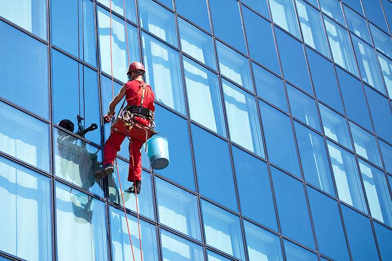 Man cleaning building glass window