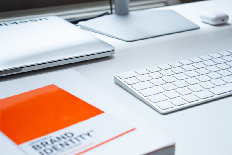 brand identity book on white desk next to laptop, keyboard and monitor