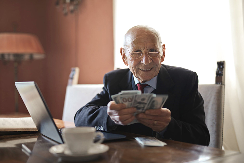 Old man counting money on his desk