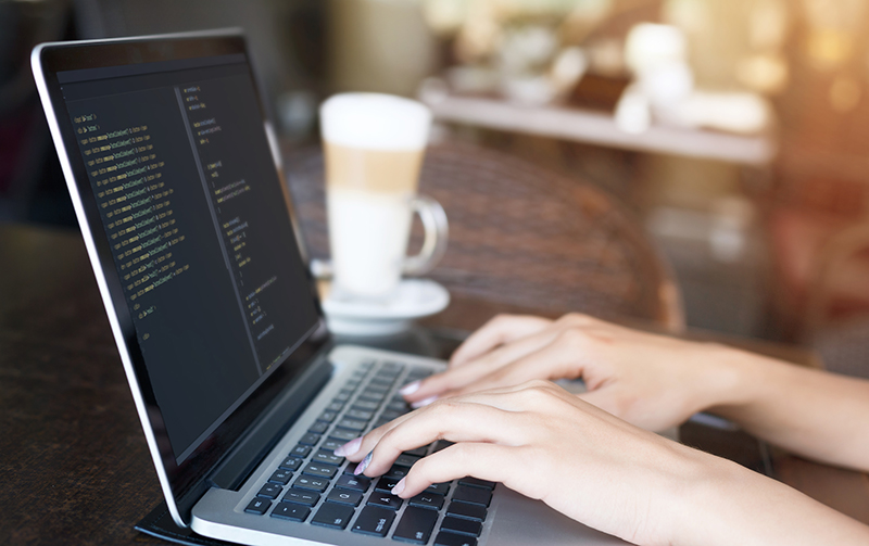 Young woman writing java script code for creating website