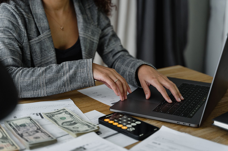 business woman working on computer software and counting money for payroll