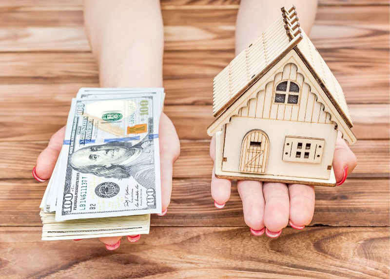 Dollar bills and house toy in person's hand