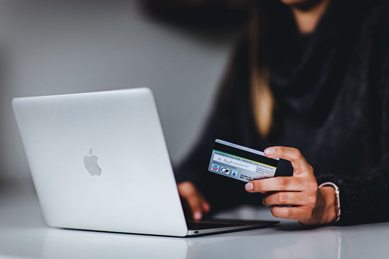 Woman holding credit card in front of silver Macbook
