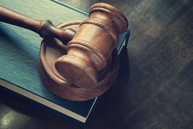 Judge gavel and legal book on wooden table