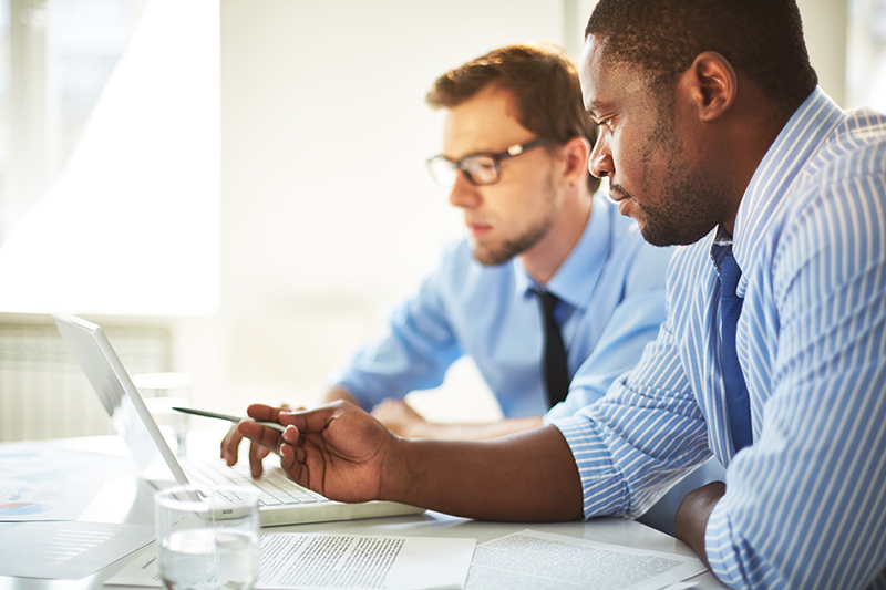 Two businessman in front of laptop