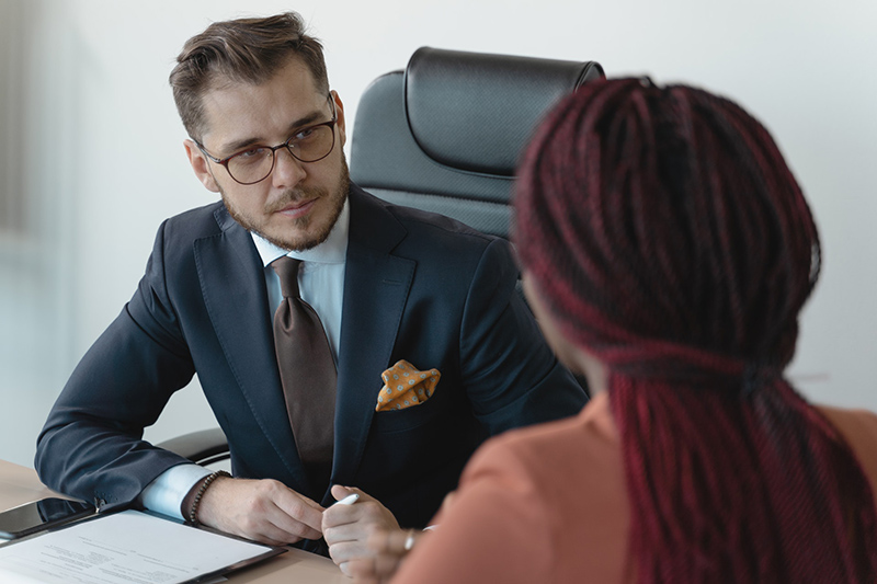 Man in black suit interviewing a woman applicant