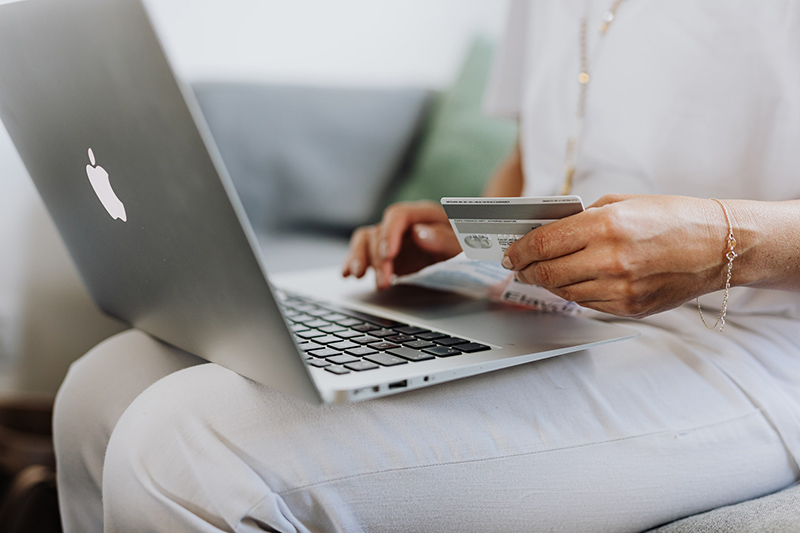 Person using MacBook and holding credit card